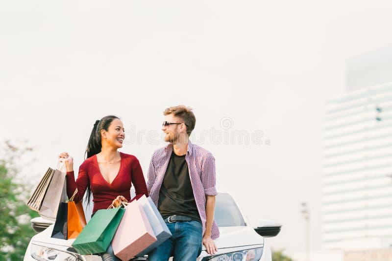 Multietniska par med shoppingpåsar som ler och sitter på den vita bilen Förälskelse, tillfällig livsstil eller shopaholic begrepp arkivfoton