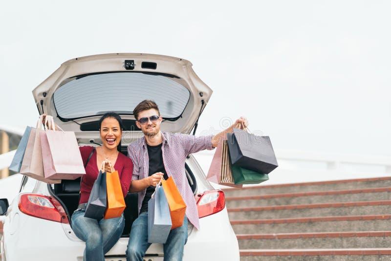Multietniska par med shoppingpåsar som ler och sitter på den vita bilen Förälskelse, tillfällig livsstil eller shopaholic begrepp royaltyfria foton