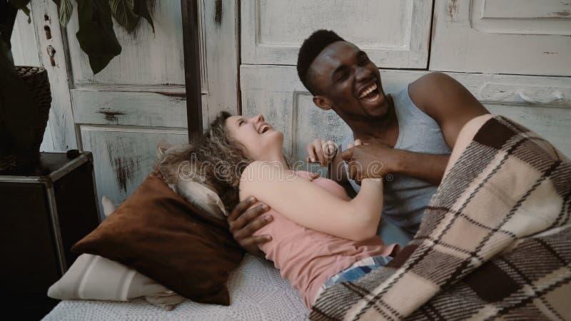 Multietniska par som ligger på säng, la som rymmer deras händer Lyckliga man och kvinnlig blick Mannen och kvinnan tycker om tid  royaltyfri foto