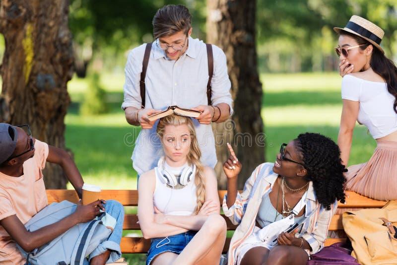 Multietniska studenter som har gyckel, medan studera tillsammans på bänk, parkerar in fotografering för bildbyråer