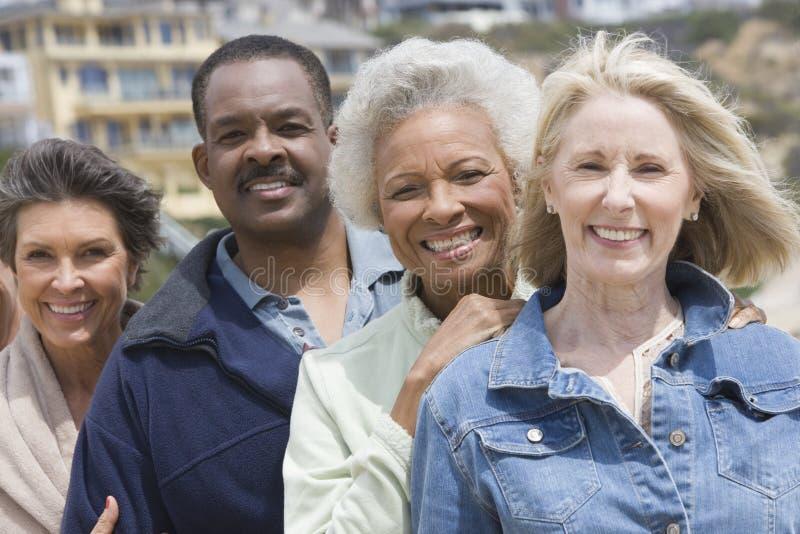 Multietniska vänner som i rad står arkivfoto