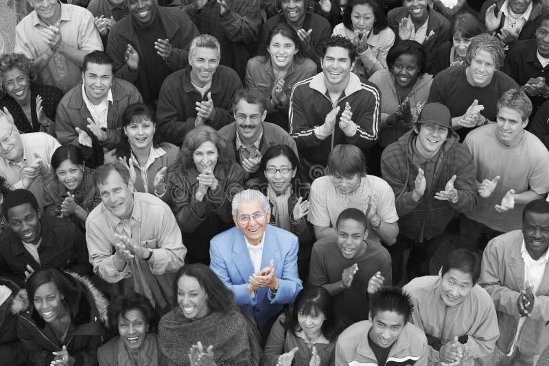 Multietniskt applådera för grupp fotografering för bildbyråer