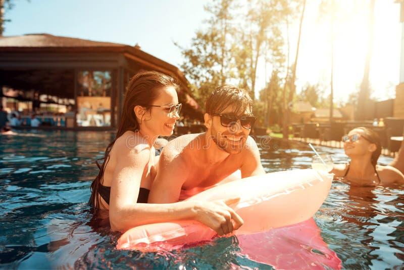 Multietniskt företag av vänner i simbassäng Företaget av ungdomarspenderar helg i pöl arkivbilder