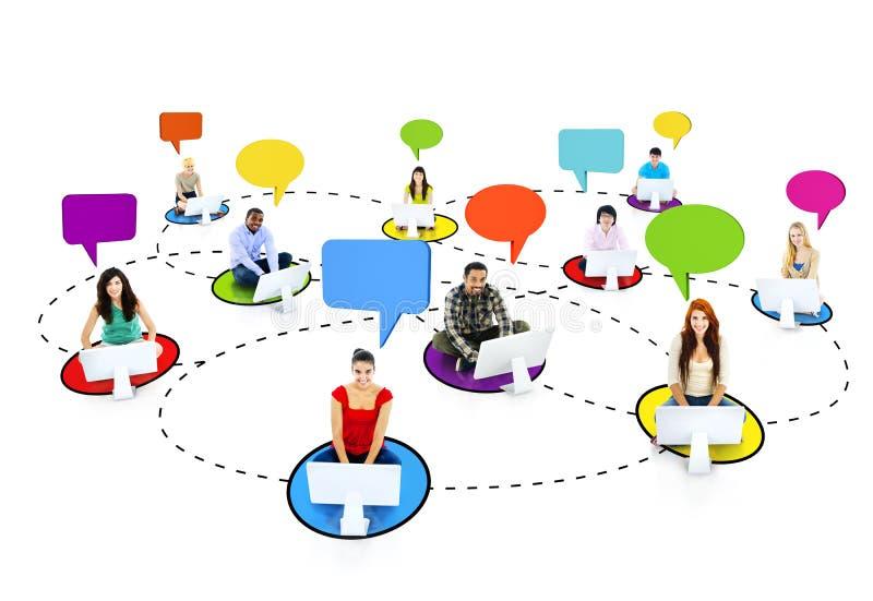 Multietniskt folk förbindelse till och med internet med anförandeBu arkivfoton