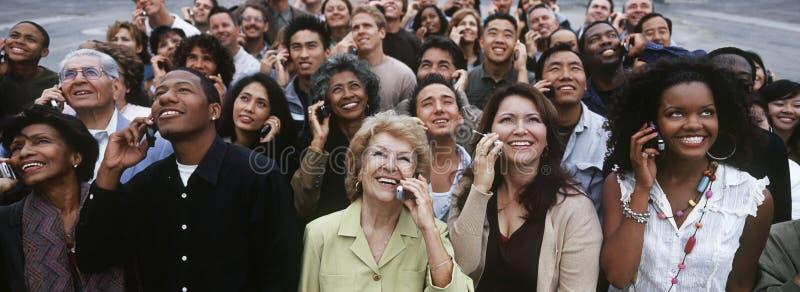 Multietniskt folk som använder mobiltelefonen arkivfoto