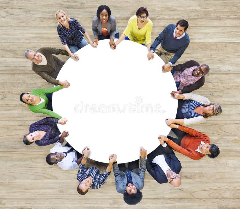 Multietniskt folk som bildar händer för ett cirkelinnehav royaltyfri foto