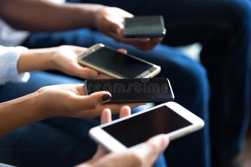 Multietniskt folk som rymmer upp telefoner i slut för handskärm upp arkivbild