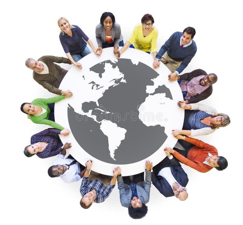 Multietniskt olikt folk i händer för ett cirkelinnehav royaltyfri foto