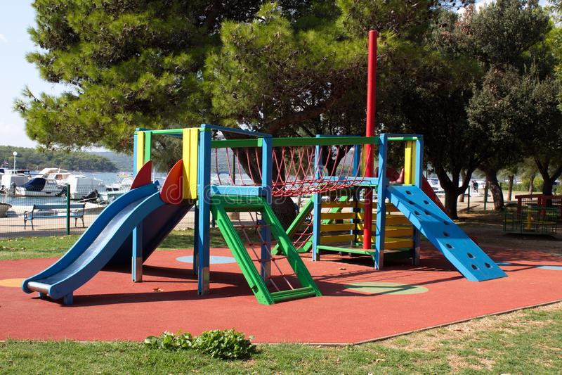 Multifunctional outdoor public playground equipment with blue plastic slide next to climbing net and wall connected with safety stock photo