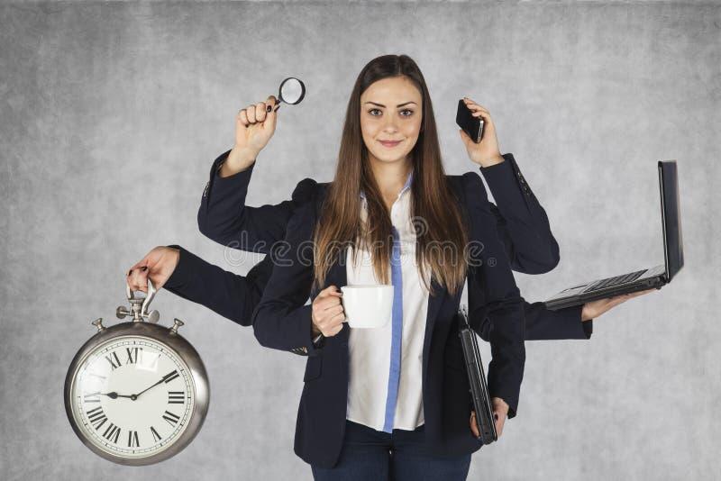 Multifunctionele bedrijfsvrouw met een groot aantal handen stock afbeeldingen