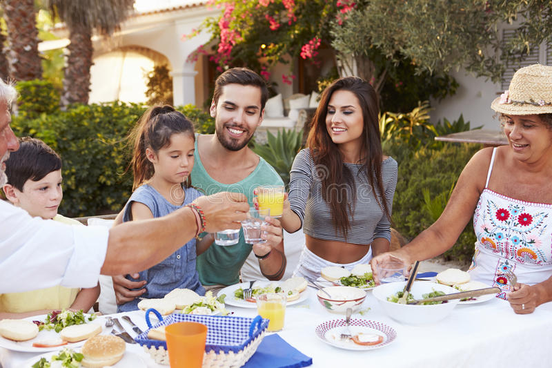 Multigeneratiefamilie die Maaltijd eten bij in openlucht samen stock foto's