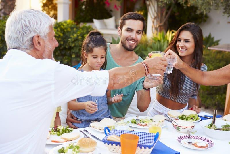 Multigeneratiefamilie die Maaltijd eten bij in openlucht samen stock afbeeldingen