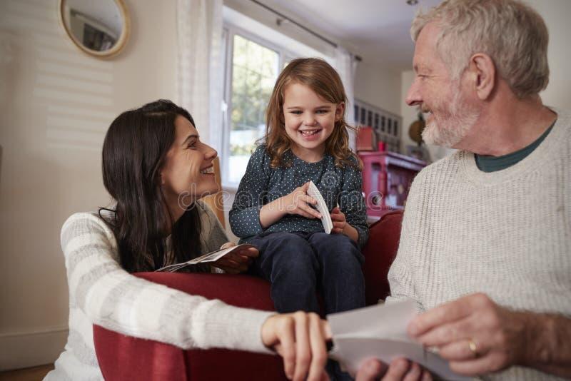 Multigeneratiefamilie die thuis Foto's bekijken stock afbeeldingen