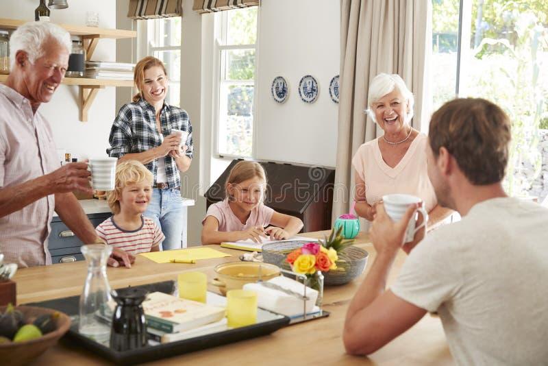 Multigeneratiefamilie die thuis in hun keuken spreken royalty-vrije stock afbeelding