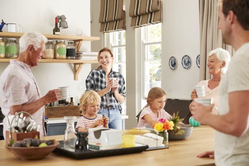 Multigeneratiefamilie die thuis in hun keuken spreken royalty-vrije stock afbeeldingen