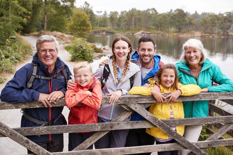 Multigeneratiefamilie die zich achter een houten omheining bevinden die aan camera, Meerdistrict, het UK kijken royalty-vrije stock foto's
