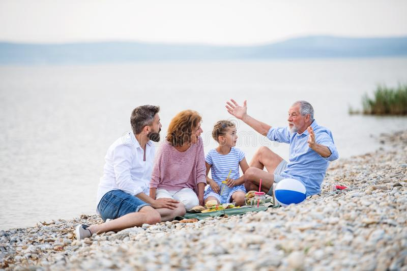 Multigeneration family on a holiday by the lake, having picnic. royalty free stock photo