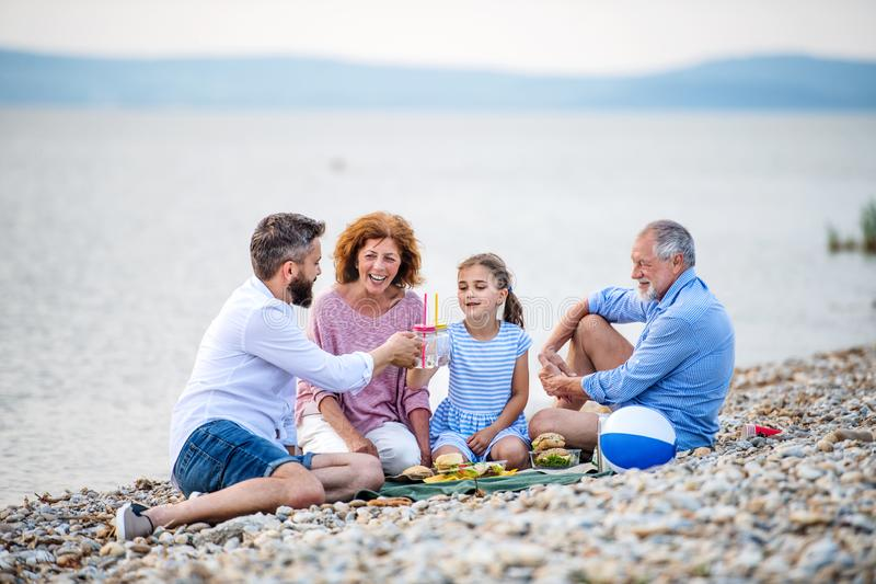 Multigeneration family on a holiday by the lake, having picnic. A multigeneration family on a holiday by the lake, having picnic stock photography