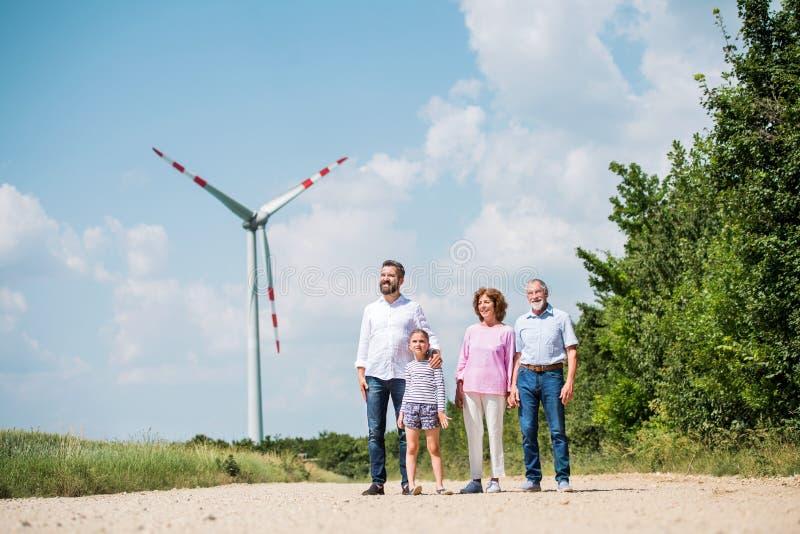Multigeneration family walking on field on wind farm. A front view of multigeneration family walking on field on wind farm stock photos