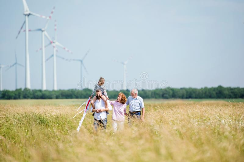 Multigeneration family walking on field on wind farm. stock photography