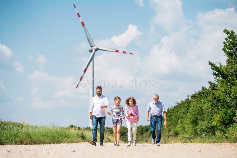 Multigeneration family walking on field on wind farm. A front view of multigeneration family walking on field on wind farm stock photo