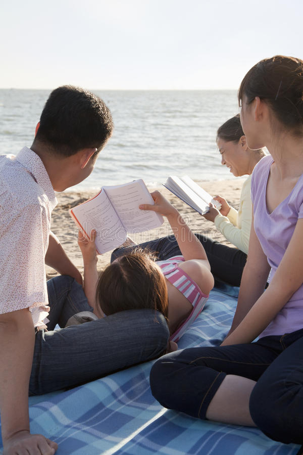Multigenerational family relaxing and reading on the beach stock images