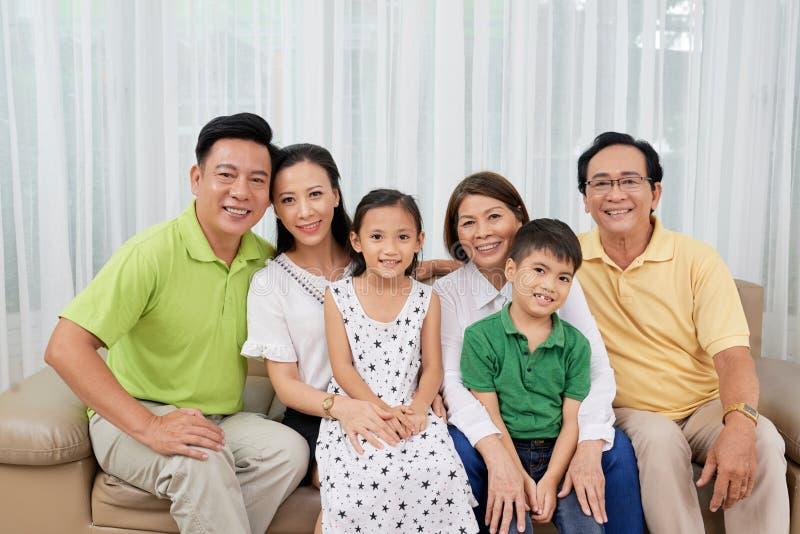 Multigenerationele Aziatische familie die zich op bank verzamelen royalty-vrije stock foto