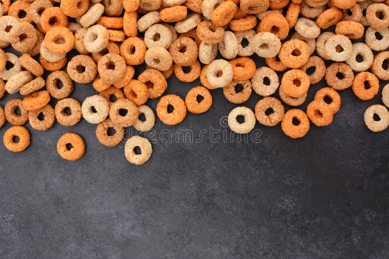 Multigrain hoops breakfast cereal border on dark grey slate royalty free stock photo