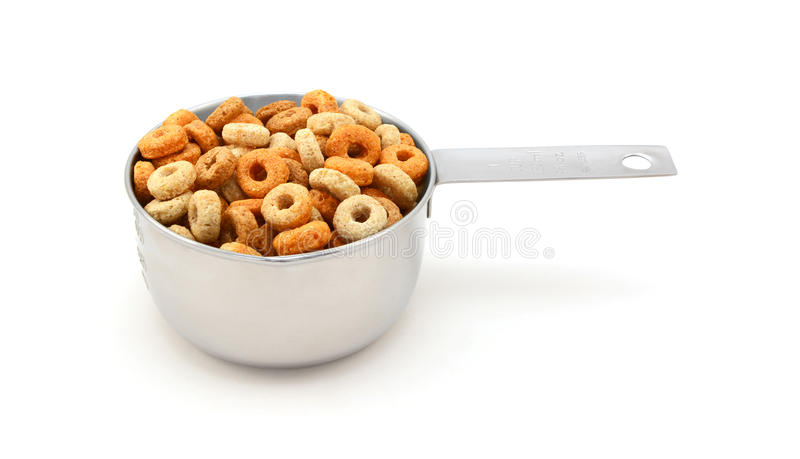 Multigrain hoops breakfast cereal in a measuring cup royalty free stock photos