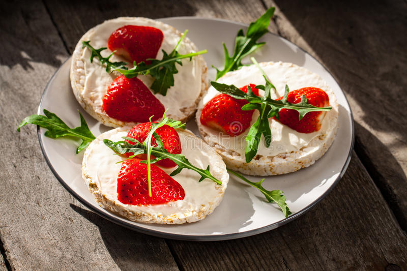 Multigrain rice cakes with strawberries fruit , soft mascarpone cheese and arugula. Multigrain rice cakes with strawberries fruit , soft mascarpone cheese and royalty free stock image