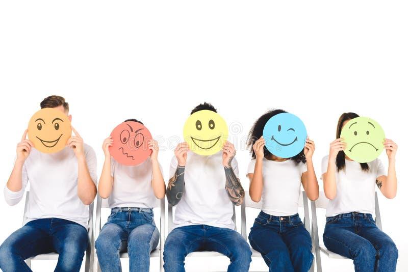 multikulturelle Freunde in den Blue Jeans, die auf Stühlen sitzen und mehrfarbige Zeichen lokalisiert halten lizenzfreies stockbild