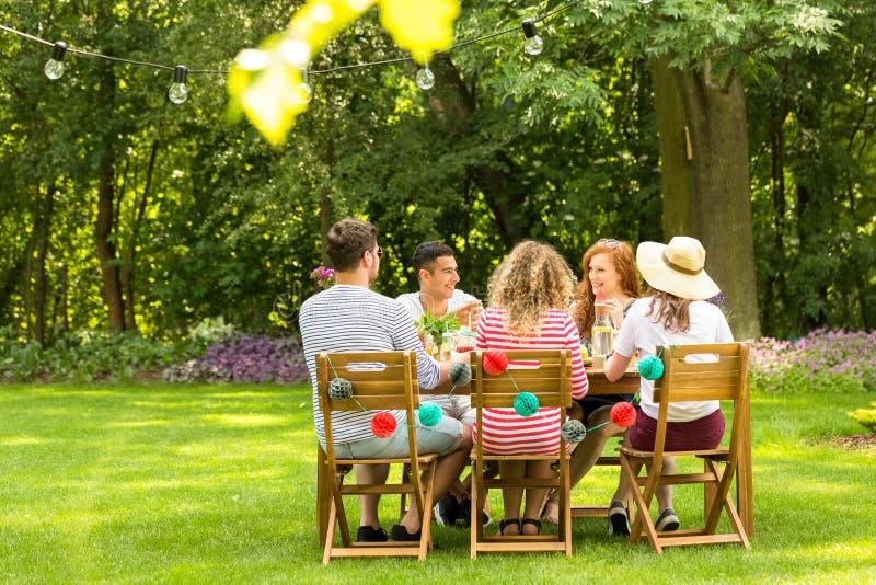 Multikulturelle Freunde, die am Tisch sitzen und im GA sprechen lizenzfreies stockbild