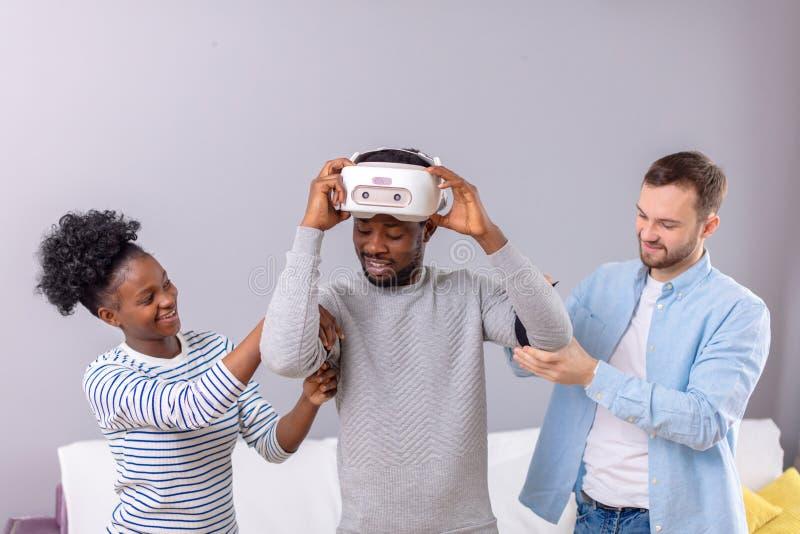 Multikulturelle Freunde helfen afrikanischem Kerl zum manade mit vr Kopfh?rer f?r Faustzeit lizenzfreies stockfoto