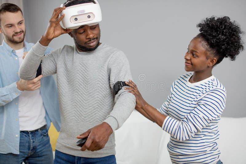 Multikulturelle Freunde helfen afrikanischem Kerl zum manade mit vr Kopfh?rer f?r Faustzeit lizenzfreies stockbild