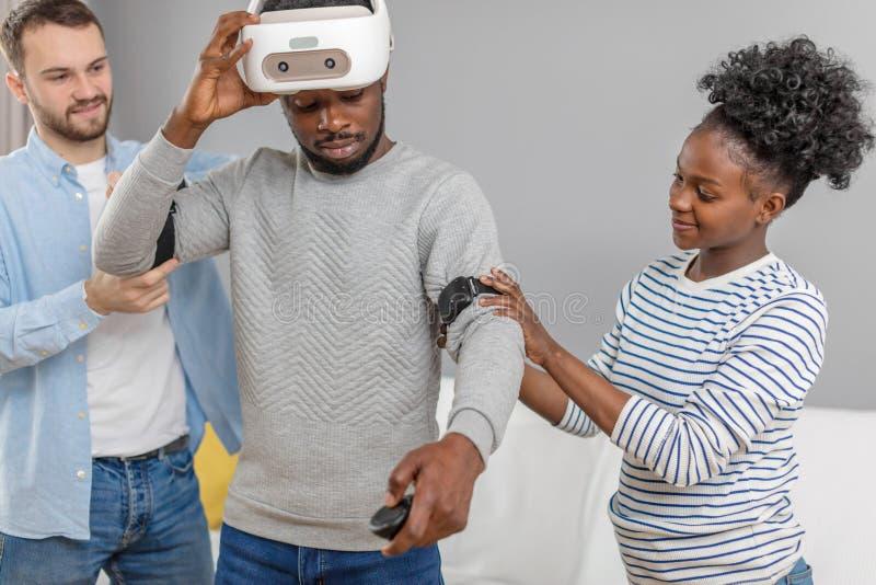 Multikulturelle Freunde helfen afrikanischem Kerl zum manade mit vr Kopfh?rer f?r Faustzeit stockfotos