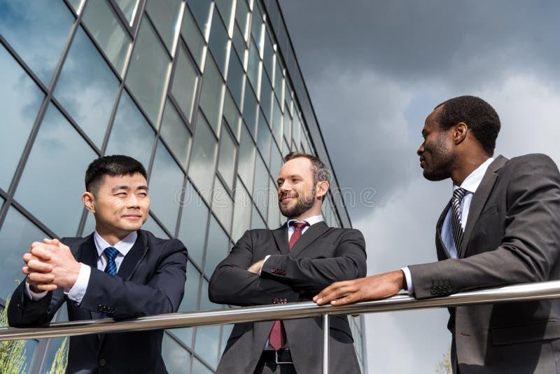 multikulturelle Geschäftsteambesprechung draußen nahe dem Bürogebäude erfolgreich lizenzfreies stockbild
