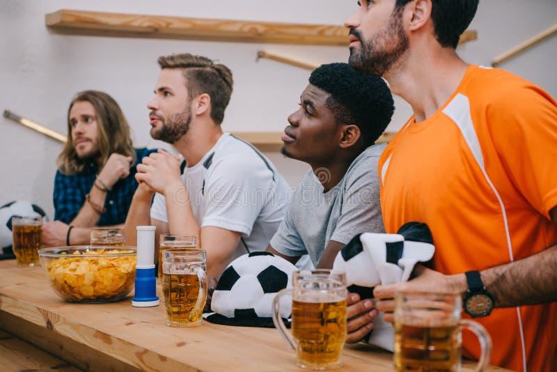 multikulturelle Gruppe männliche Fußballfane mit Fußballhüten lockern Hornspäne und aufpassendes Fußballspiel des Bieres auf stockfoto