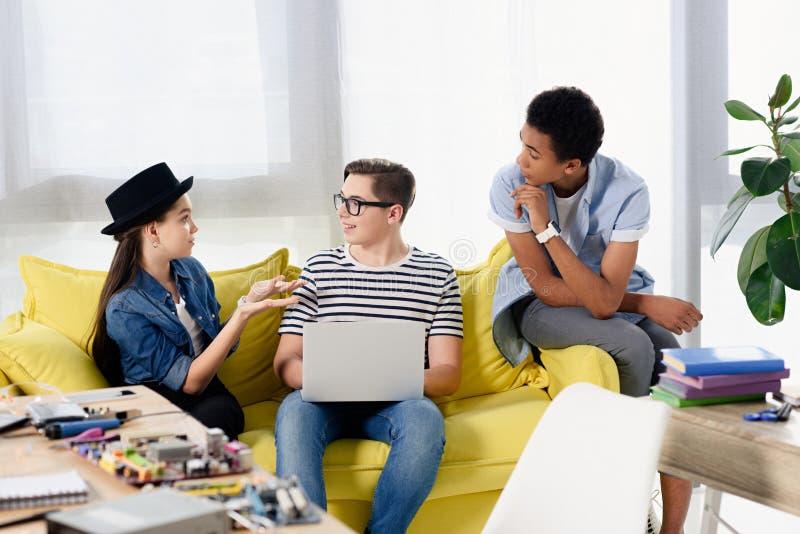 multikulturelle Jugendliche, die auf Sofa mit Laptop sitzen stockfotografie