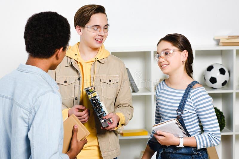 multikulturelle Jugendliche, die Computermotherboard und -bücher sprechen und halten stockfotos