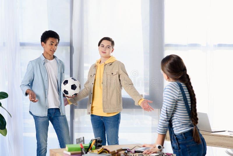 multikulturelle Jugendliche, die Fußballball halten und Freund betrachten stockfotos