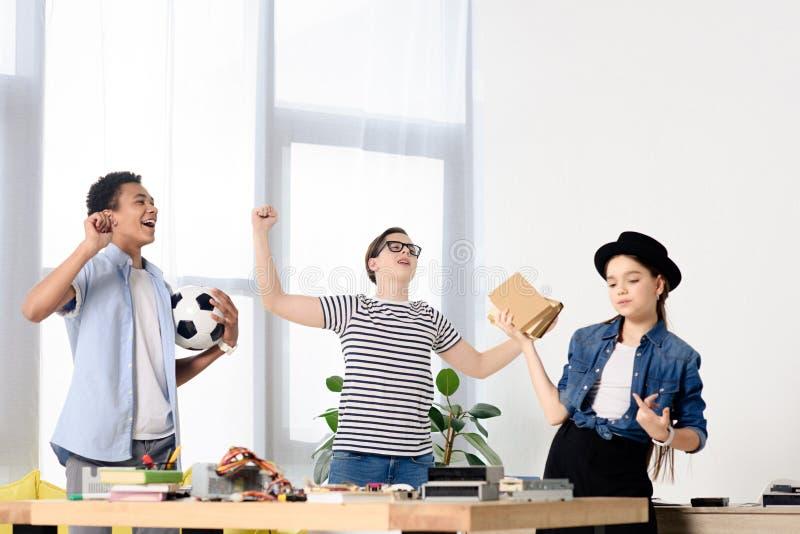 multikulturelle Jugendliche, die ja Gesten zeigen und Fußballball halten stockbild