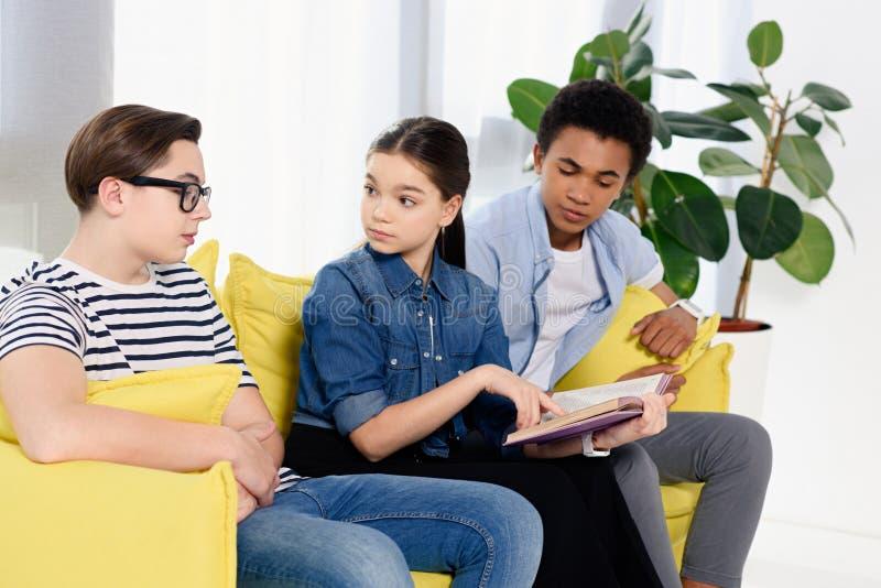 multikulturelle Jugendliche, die mit Buch sitzen stockfoto