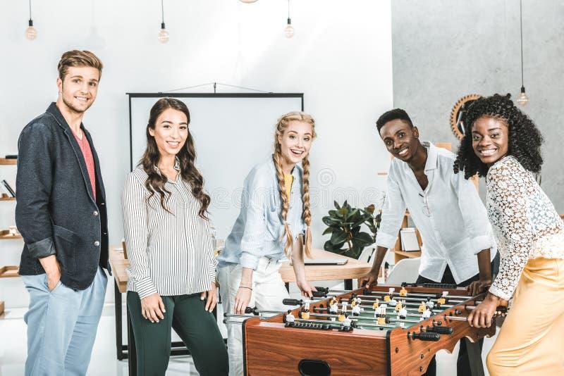 multikulturelle lächelnde Geschäftsleute, die Kamera beim Spielen des Tischfußballs betrachten stockbilder