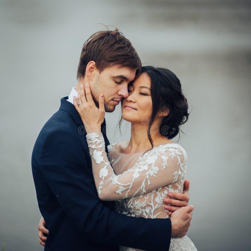Multikulturelle Paare, die auf See mit altem Schloss sich umarmen stockfotos