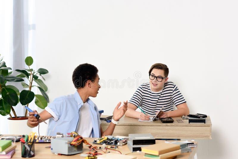 multikulturelle sprechende Jugendliche beim Reparieren des Computermotherboards stockfotografie