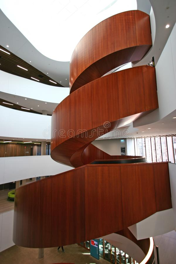 Multistory indoor atrium with suspended wood spiral stairs like dancing ribbon at University of Sydney Business School, Australia stock photo