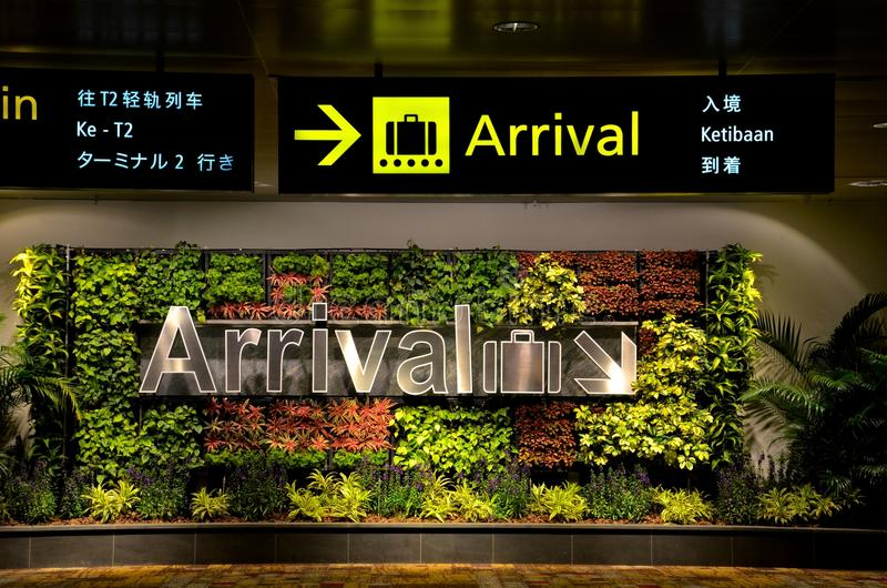 Multilingual arrival sign and flowers at airport