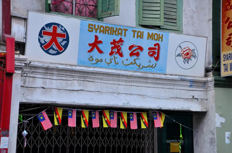 Multilingual shop sign in mandarin Chinese Malay and Arabic Jawi Malay with flags Kuching Sarawak Malaysia. Kuching, Malaysia - October 13, 2018: A Chinese shop stock photos