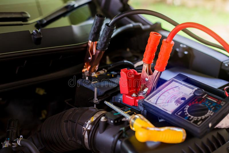 Multimeter for check voltage in battery with blurry yellow screw driver for repair service. Auto mechanic working in garage. royalty free stock photography