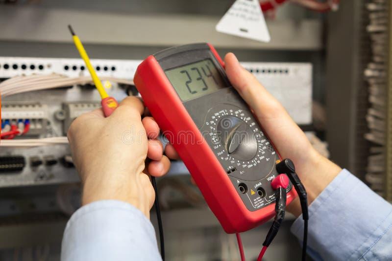 Multimeter in elektricienhanden stock fotografie